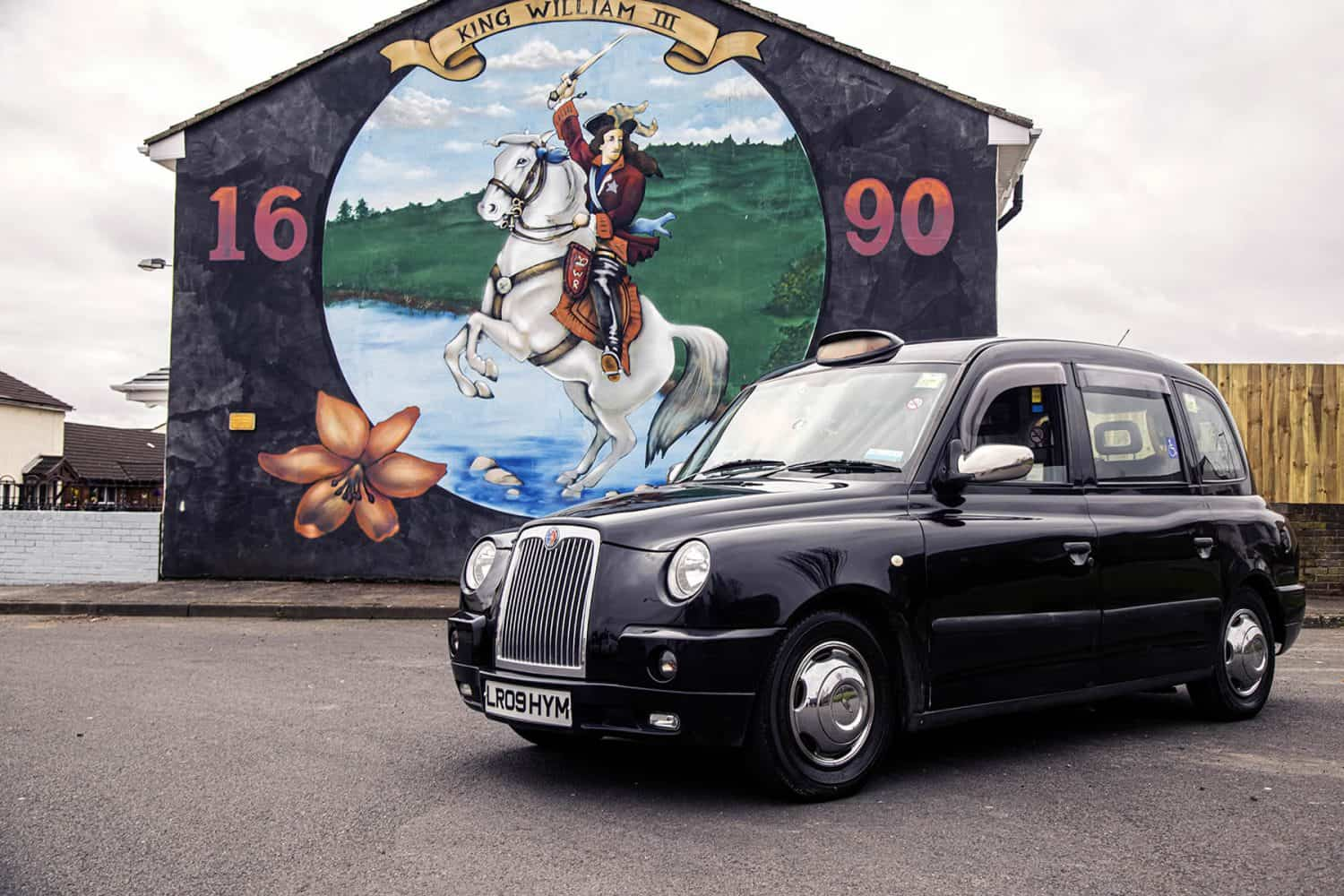 Belfast Mural Tours taxi cab parked at King William Mural in Shankill Belfast