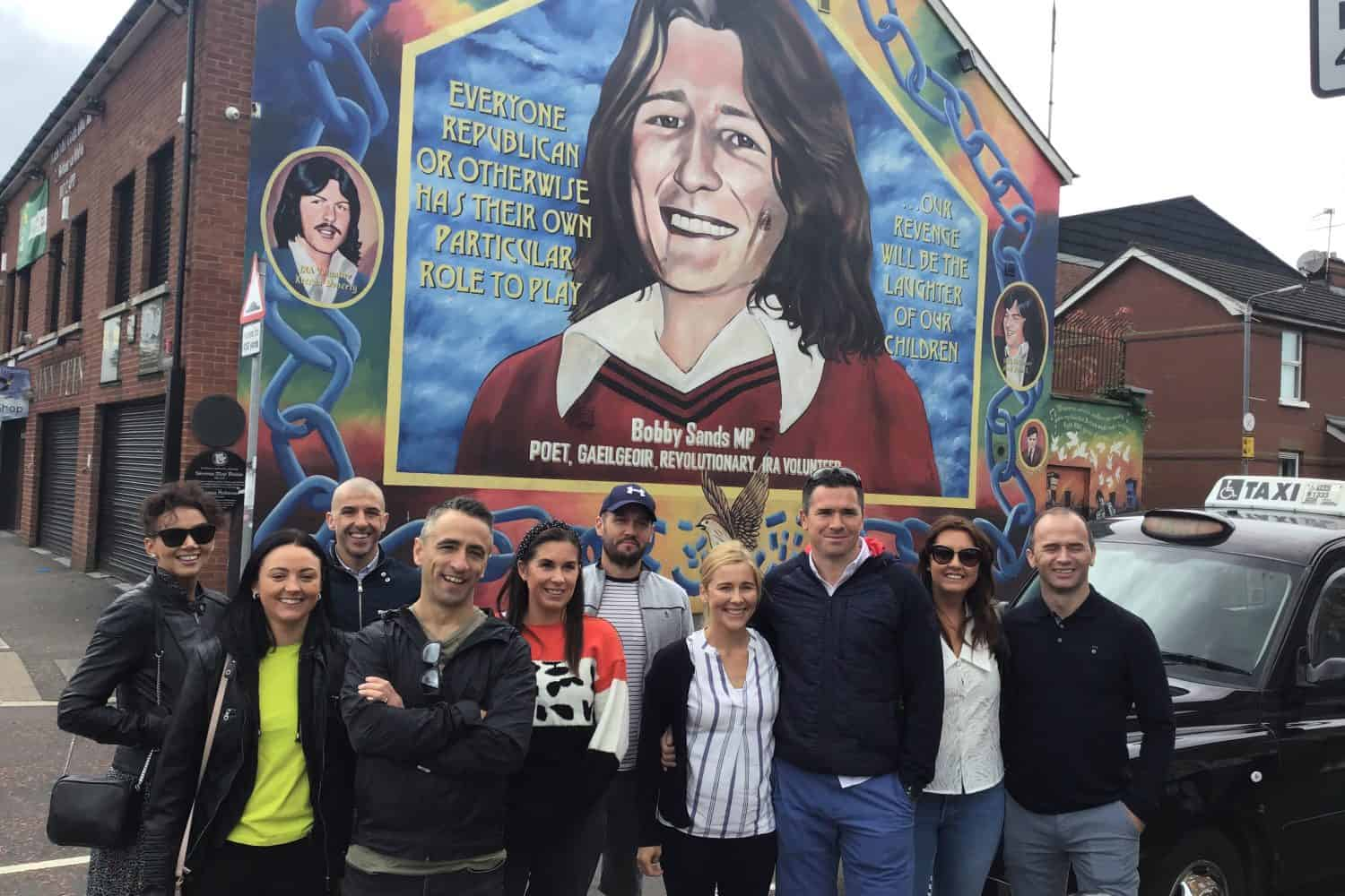 Belfast Mural Tours Passengers at Bobby Sands Mural in the Falls