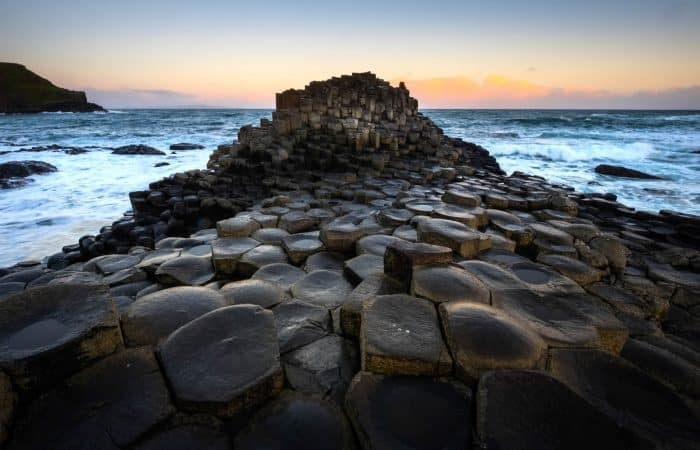 Hexagonal Stone Columns at Giants Causeway with sunset in the background
